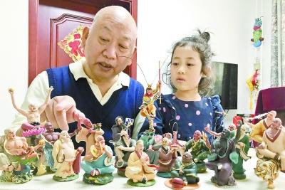 4张俊显在家给外孙女讲解2003年抗击SARS期间创作的面人作品《十八罗汉斗悟空》。